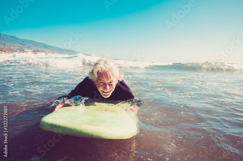 Photo one senior trying surfing alone in the water of the beach and learning surf - ma