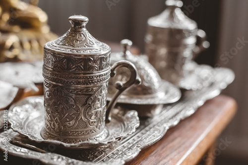 Fototapeta Closeup shot of an antique silver tea set with a blurry background
