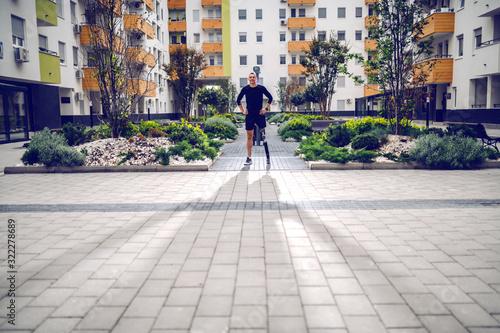 Αφίσα Full length of handsome smiling sportsman with artificial leg standing with hands on hips outdoors surrounded by buildings
