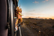 Leinwandbild Motiv beautiful caucasian young woman travel outside the car with wind in the curly hair, motion and movement on the road discovering new places during a nice sunset, enjoy and joyful freedom concept