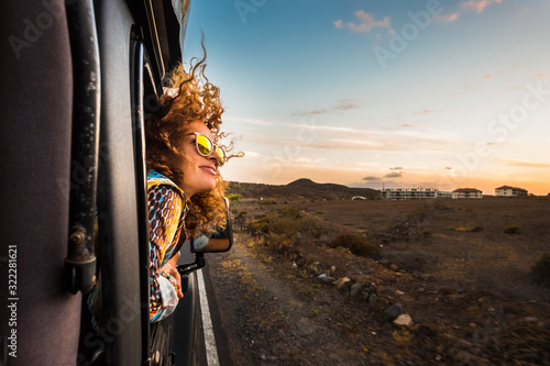 Obraz na plátne beautiful caucasian young woman travel outside the car with wind in the curly ha