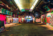 London, UK/Europe; 21/12/2019: Leake Street, Underground Tunnel With Graffiti Covered Walls In London. Scene With Pedestrians And Graffiti Artists.