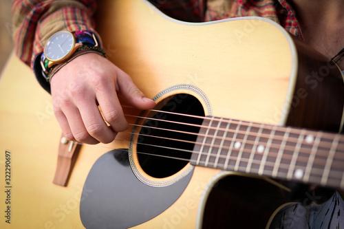 Close up image of man strumming guitar Fototapeta