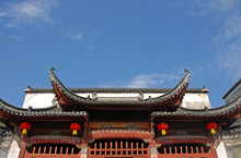Xidi Ancient Town In Anhui Province, China. Zhuimu Tang Is A Hall In The Old Town Of Xidi. Image Shows The Traditional Chinese Roof Set Against The Blue Sky And Red Lanterns. Hall In Xidi Ancient Town