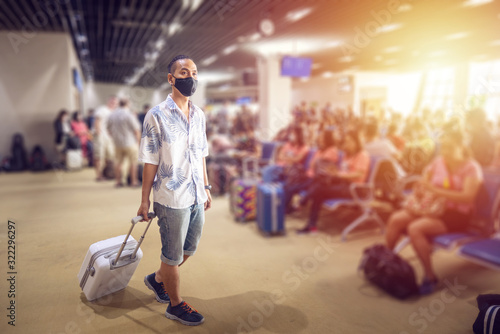 Obraz Asian tourist with luggage ,wearing mask to prevent during travel time at the airport terminal for protect from the new Coronavirus 2019 infection outbreak situation - fototapety do salonu