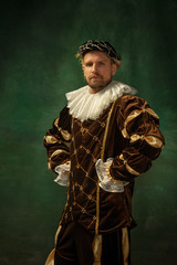 Posing thoughtful. Portrait of medieval young man in vintage clothing standing on dark background. Male model as a duke, prince, royal person. Concept of comparison of eras, modern, fashion.