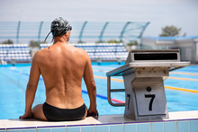 Young Muscular Swimmer Is Sitt...