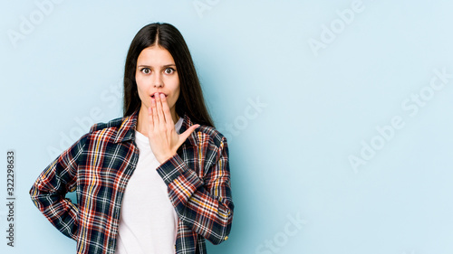 Young caucasian woman isolated on blue background shocked, covering mouth with hands, anxious to discover something new Wallpaper Mural