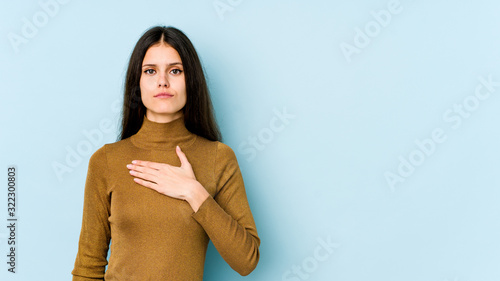 Young caucasian woman isolated on blue background taking an oath, putting hand on chest Wallpaper Mural