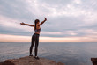 white slim athletic young woman in sportswear stands on a rock against the background of the sea and sky at sunset