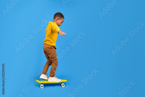 Boy African-American boy in everyday clothes skateboards having fun and smiling. Hands arranged for balancing on blue background with space for text. Concept of activity and happy childhood.