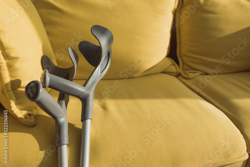 Crutches near yellow sofa with sunlight