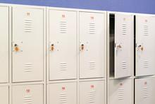A Row Of Grey Metal School Lockers With Keys In The Doors. Storage Locker Room In Corridor Of Educational Institution