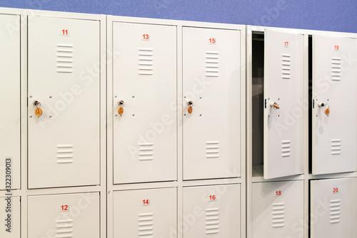 Fototapeta A row of grey metal school lockers with keys in the doors. Storage locker room in corridor of educational institution obraz