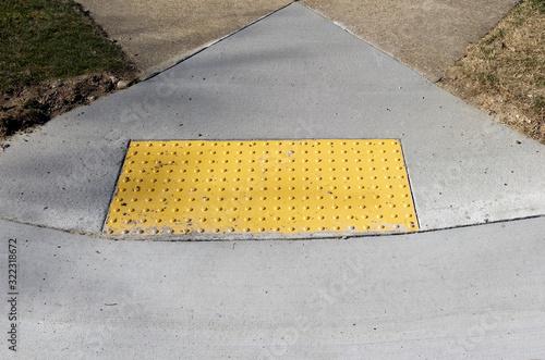Foto Sidewalk curb ramp with bumpy anti slip pad.
