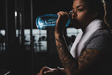 African American Girl With Tattoo Drinking Water While Holding Sports Bottle In Gym