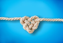 White Rope In Heart Shape Knot On Background. Love Concept.