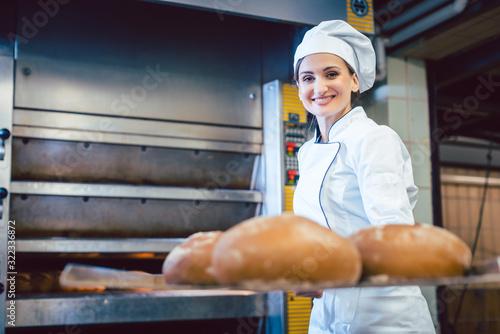 Fototapeta Baker woman showing freshly baked bread on shovel