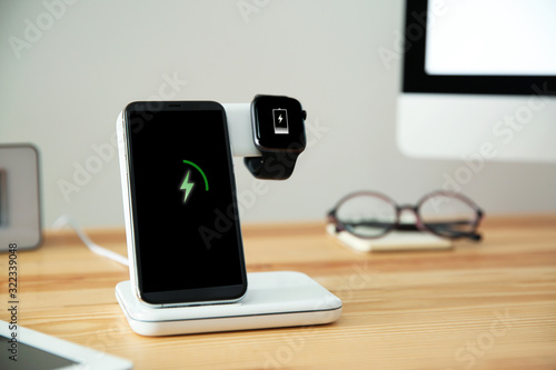 Obraz na plátně Mobile phone and smartwatch with wireless charger on wooden table