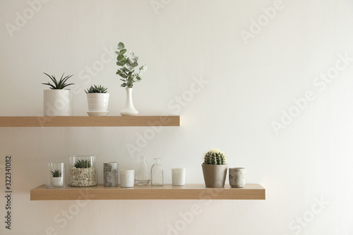 Fotografía Wooden shelves with plants and decorative elements on light wall