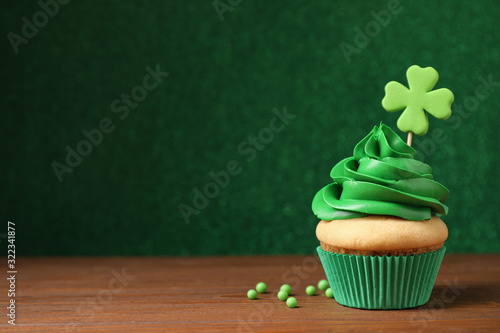Fototapeta Delicious decorated cupcake on wooden table, space for text. St. Patrick's Day celebration obraz