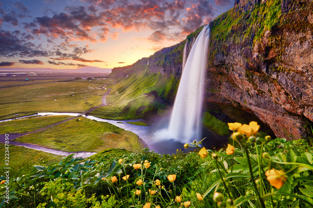 Fototapeta Incredible sunset on Seljalandsfoss. One of the most beautiful waterfalls on the Iceland, Europe. Popular and famous tourist attraction summer holiday destination in on South Iceland. Travel postcard.