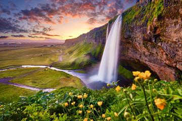 Nevjerojatan zalazak sunca na Seljalandsfossu. Jedan od najljepših slapova na Islandu, u Europi. Popularno i poznato turističko odredište za ljetovanje na Južnom Islandu. Putnička razglednica.
