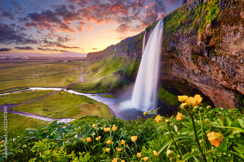 Incredible sunset on Seljalandsfoss. One of the most beautiful waterfalls on the Iceland, Europe. Popular and famous tourist attraction summer holiday destination in on South Iceland. Travel postcard. - 322347890