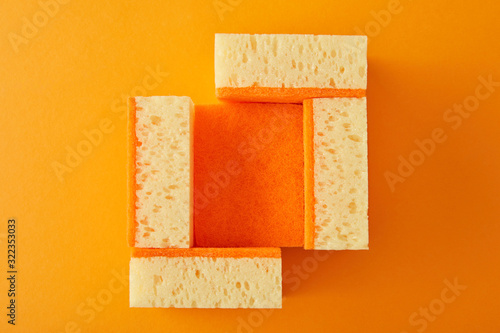 top view of yellow sponges for house cleaning on orange