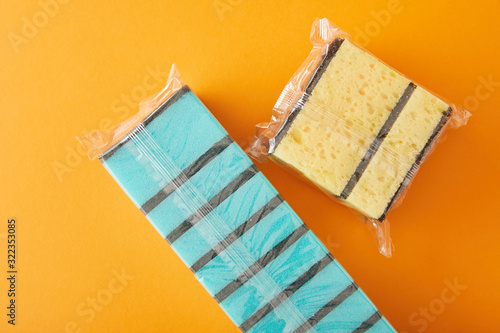 top view of packed blue and yellow sponges for house cleaning on orange