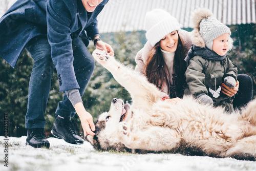 Happy european family with big dog having fun at winter. Canvas Print