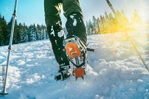 Close up shot of mountain boots with crampons and snow gaiters with backlight sunbeams and snowy spruces on the background Wallpaper Mural