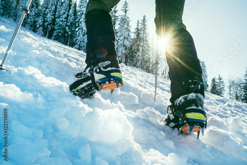 Close up shot of mountain boots with crampons and snow gaiters with backlight sun beams and snowy spruces on background Wallpaper Mural