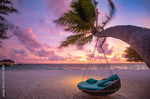 Fototapeta Tropical sunset beach background as summer landscape panorama with beach swing or hammock and white sand and calm sea beach banner. Perfect beach scene vacation or summer holiday concept obraz
