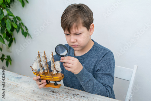A beautiful boy of 10 years old, a student of the 3rd class, studies the structure of a wooden model of a handmade ship through a magnifying glass Wallpaper Mural