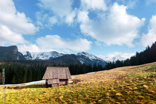 Fototapeta Old wooden hut and cloudy sky in spring High Tatras mountains in Kalatowki meadow, Zakopane, Poland. Landscape photography obraz