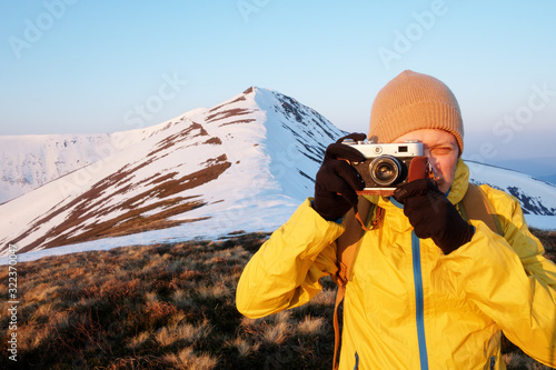 Fototapeta Photographer in yellow jacket taking photo on snowy winter field obraz