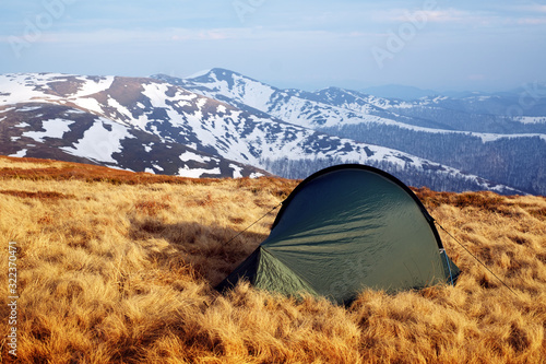 Fototapeta Green tent on amazing meadow in spring mountains. Landscape photography, travel concept obraz