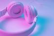 Retro 90s style photo of white stylish wireless headphone in neon lights. Music concept.