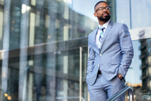 Handsome Male African American Business Man CEO In A Stylish Chic Suit At The Workplace, Standing Confidently In Front Of Financial Building