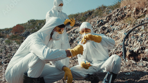 Fototapeta Close-up scientists in chemical suits observing contamined landscape with trash rocks on dump
