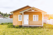 Small Tiny Wooden Frame House With Sundeck And White Windows And Door As A Country Residence In Sunny Summer Day
