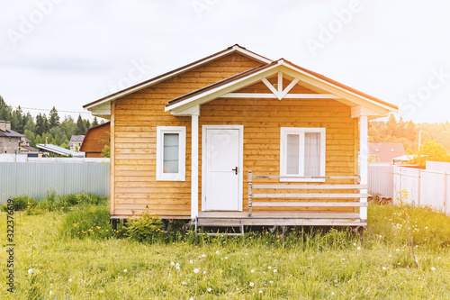 Photo Small tiny wooden frame house with sundeck and white windows and door as a count