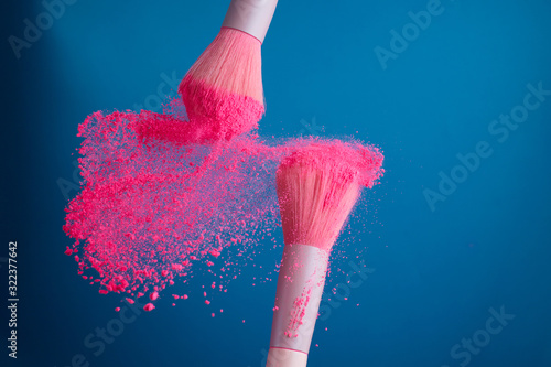 Fotografía close-up photo of two professional make-up brushes with pink powder in motion on