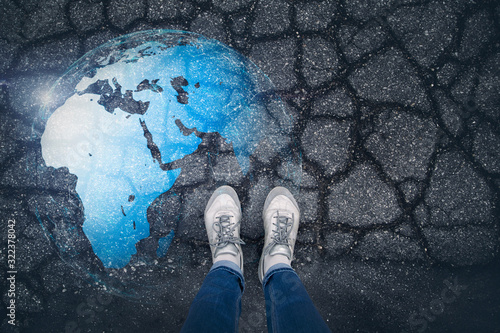 Obraz na plátně Woman stands on cracked floor with illustrated earth globe