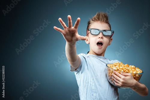 A boy holding popcorn in his hands watching a movie in 3D glasses, fear, blue...