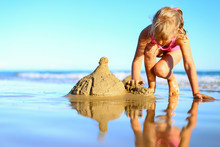 Cute Little Girl Spend Holidays In Pink One-piece Swimsuit, Builds Sand Castle, Plays In The Water On The Shore Of The Blue Sea. Vacation With Kids On Beach On A Warm Sunny Summer Day Before Sunset