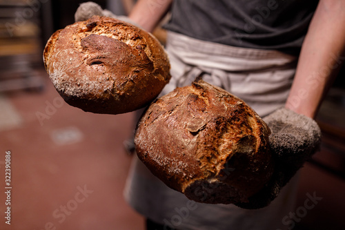Leinwand Poster Bäcker presentiert bio Brot in der Backstube