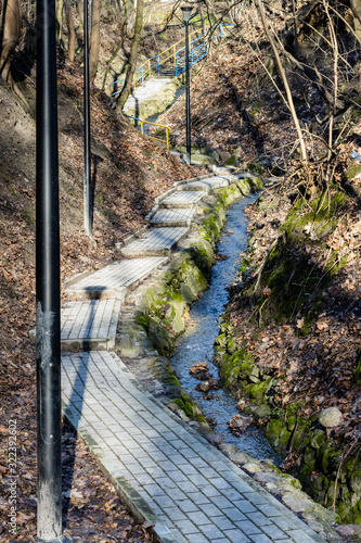 Walking path leading uphill (stairs) in outdoor city park. Narrow stream flowing next to trail. Serock, Poland, Europe.