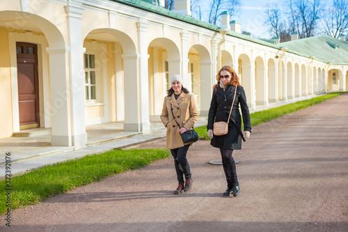 Smiling girl takes a walk in royal Oranienbaum park near Grand Palace at spring Wallpaper Mural